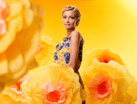 Beautiful young blond woman in colourful dress among big yellow flowers photo