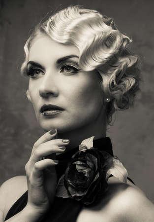 Monochrome portrait of elegant blond retro woman  in dress with beautiful rose flower photo