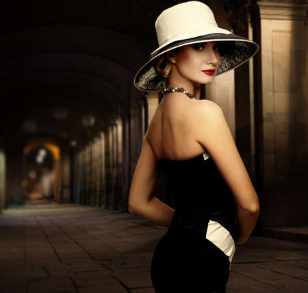 nostalgy: Woman in black dress and big white hat alone outdoors at night Stock Photo