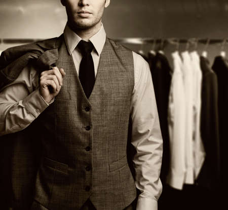 closets: Businessman in classic vest against row of suits in shop Stock Photo