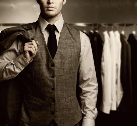 gentlemen: Businessman in classic vest against row of suits in shop Stock Photo