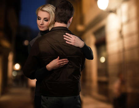 parting: Blond woman embracing man in brown vest outdoors at night
