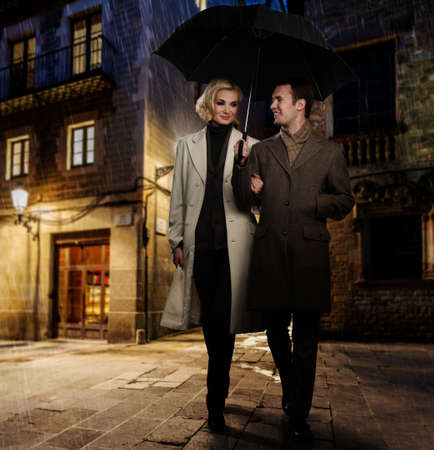 Elegant couple in autumnal coats walking in the rain outdoors at night photo