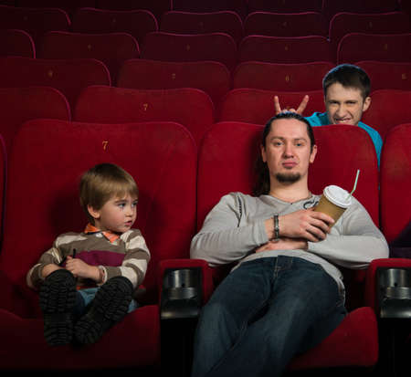 Man with boy in cinema with funny guy behind them photo