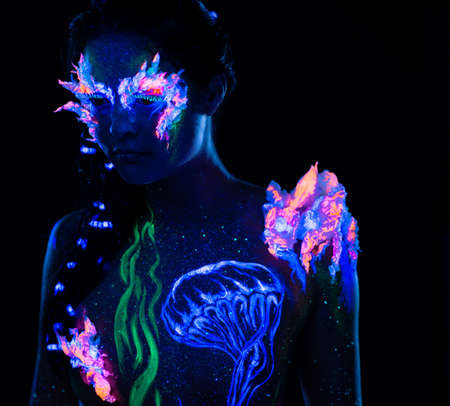 fantasy makeup: Beautiful woman with body art glowing in ultraviolet light