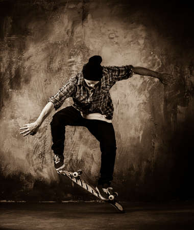 boy skating: Young man in hat and shirt performing stunt on skateboard