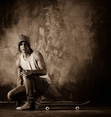Young man in hat and jeans sitting near skateboard photo