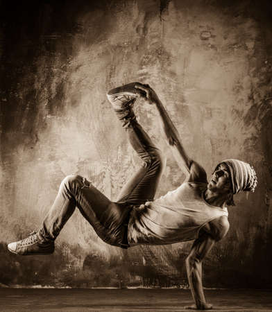 Toned picture of young man  doing acrobatic movements against grunge wall photo