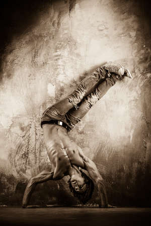 Toned picture of young man with torso doing acrobatic movements  photo