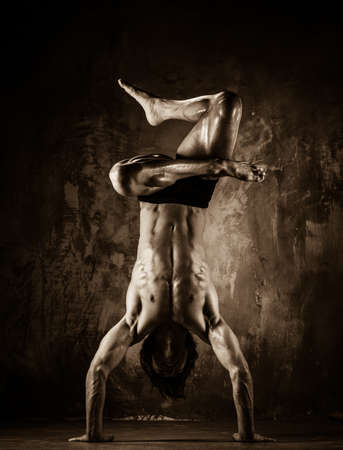 Toned picture of young man with nude torso doing acrobatic movements  photo
