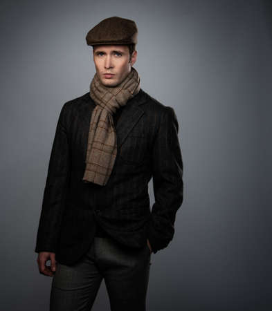 Young man in brown jacket wearing cap and scarf isolated on grey background  photo