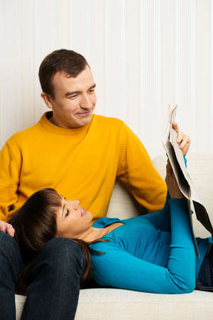 Cheerful young couple on sofa in home interior with newspaper Stock Photo - 18548111