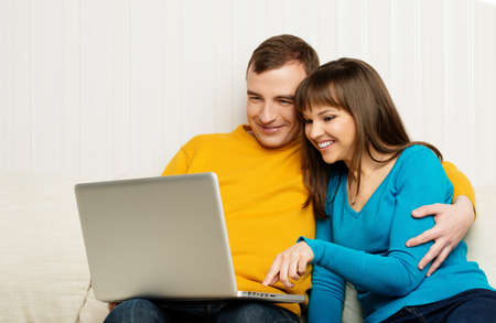 inet: Smiling man and woman with laptop sitting on sofa in home interior Stock Photo