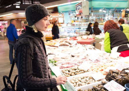 Young woman choosing seafood on market photo