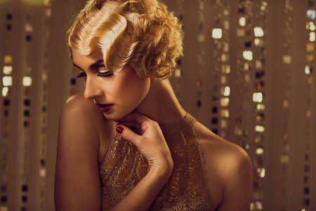 aretes: Elegante mujer retro rubia en traje de oro con un hermoso peinado y labios pintados de rojo