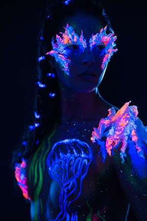 ultraviolet: Beautiful woman with body art glowing in ultraviolet light