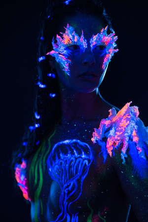 body paint: Mujer hermosa con el arte del cuerpo que brilla intensamente en luz ultravioleta