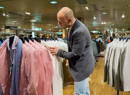 choosing clothes: Middle-aged man choosing clothes in a shopping mall  Stock Photo