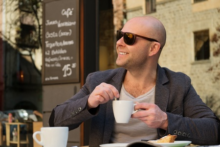 Cheerful middle-aged man with coffee cup in street cafe photo