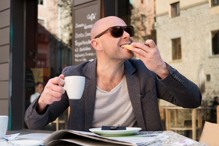 MIddle-aged man enjoying coffee with piece of cake in street cafe