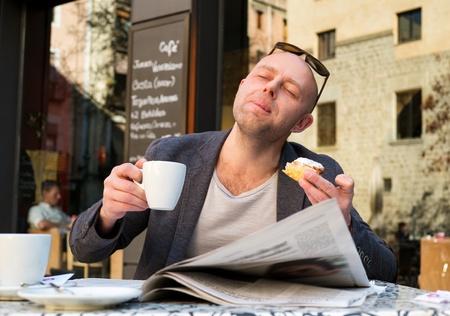 Mann mittleren Alters genießen Kaffee mit Kuchen in Straßencafé