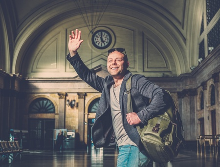 MIddle-aged tourist with backpack meeting someone in railroad station building photo