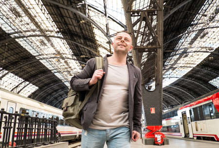 MIddle-aged traveler with backpack on train station platform photo