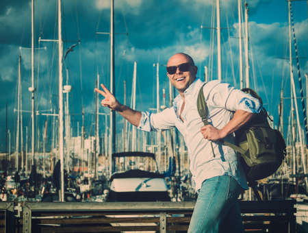 Happy middle-aged man with backpack against yacht port photo