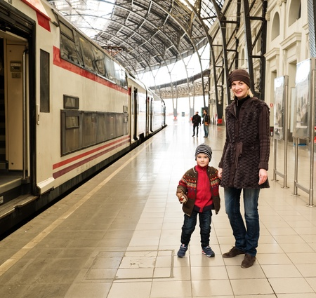 departures: Happy mother with her son on train station platform