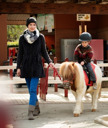 pony ride: Mother riding her son on a pony wearing protective helmet