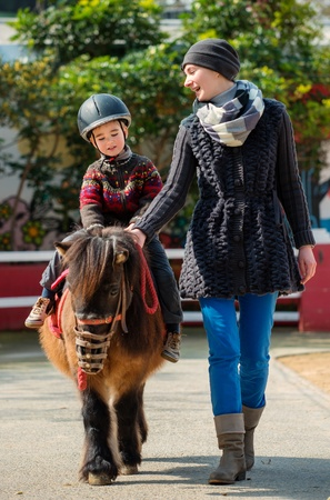 zoo youth: Mother riding her son on a pony wearing protective helmet