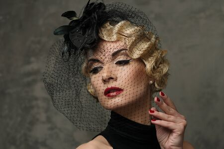 Elegant blond retro woman  with red lipstick wearing little hat with veil  photo
