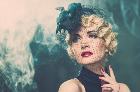 Elegant blond retro woman   wearing little hat with veil in smoke photo