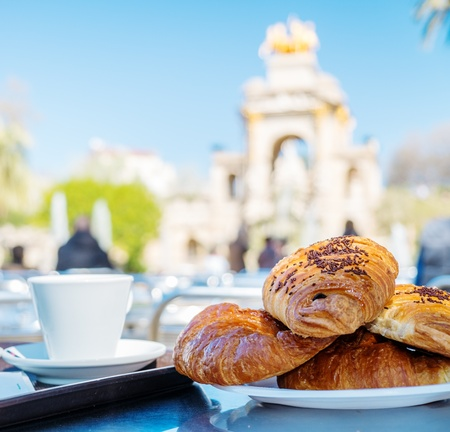 Tasty croissants with cup of coffee against famous fountain view in Barcelona photo