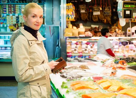 fish market: Young blond woman buying fish on market