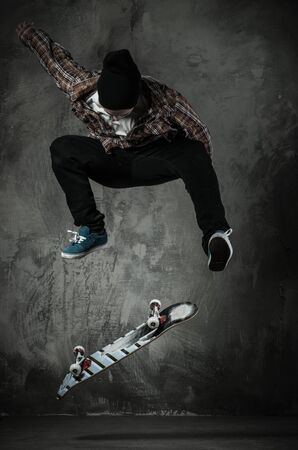Young man in hat and shirt performing stunt on skateboard photo