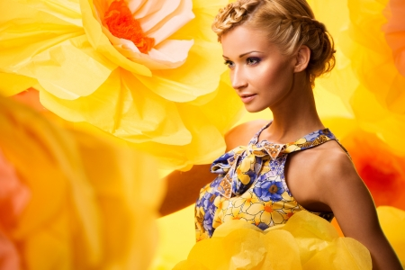 yellow dress: Beautiful young cheerful blond woman in colourful dress among big yellow flowers