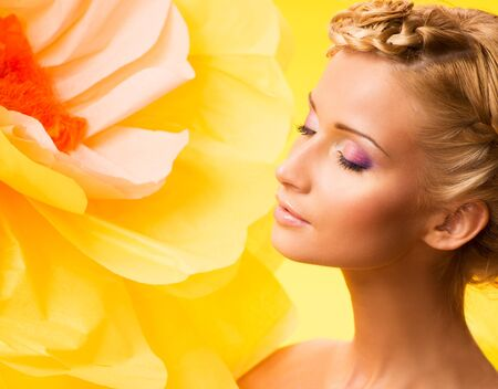 among: Beautiful young blond woman with closed eyes in colourful dress among big yellow flowers