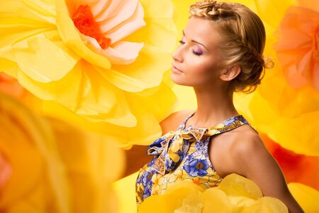 Beautiful young blond woman with closed eyes in colourful dress among big yellow flowers photo