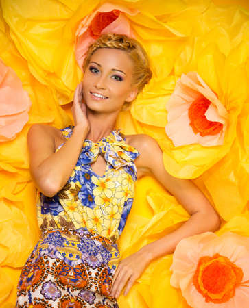 Beautiful young blond woman in colourful dress lying among big yellow flowers photo