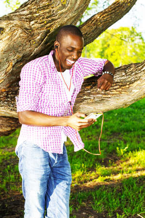 Smiling young african american man in shirt standing near tree and listens music in a park