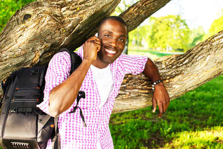 Young smiling african american man with rucksack in a park talking over mobile phone photo