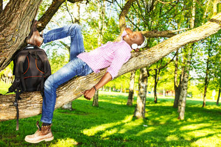 Young smiling african american lying on a tree branch in a park  and listens to music photo