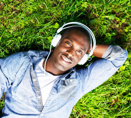 Young happy smiling african american lying on a grass and listens to music in a park photo