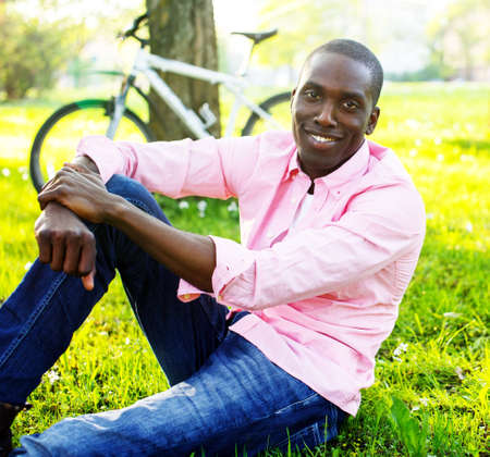 Young happy smiling african american wearing pink shirt with bicycle behind him in a park photo