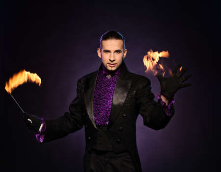 conjuror: Young brunette magician in stage costume performing flame tricks