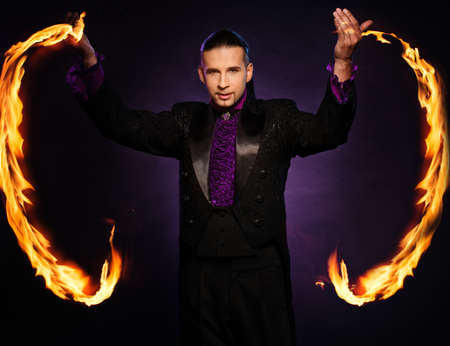 Young brunette magician in stage costume performing flame tricks  photo