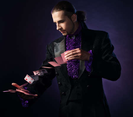 Young brunette magician in stage costume showing card tricks  photo