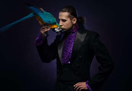 mago: Joven mago morena guapo en traje de la etapa con su loro entrenado