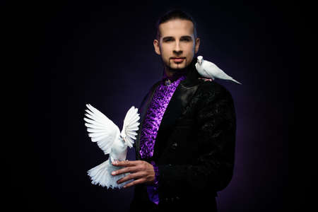 Jonge knappe brunette tovenaar man in fase kostuum met zijn getrainde witte duiven